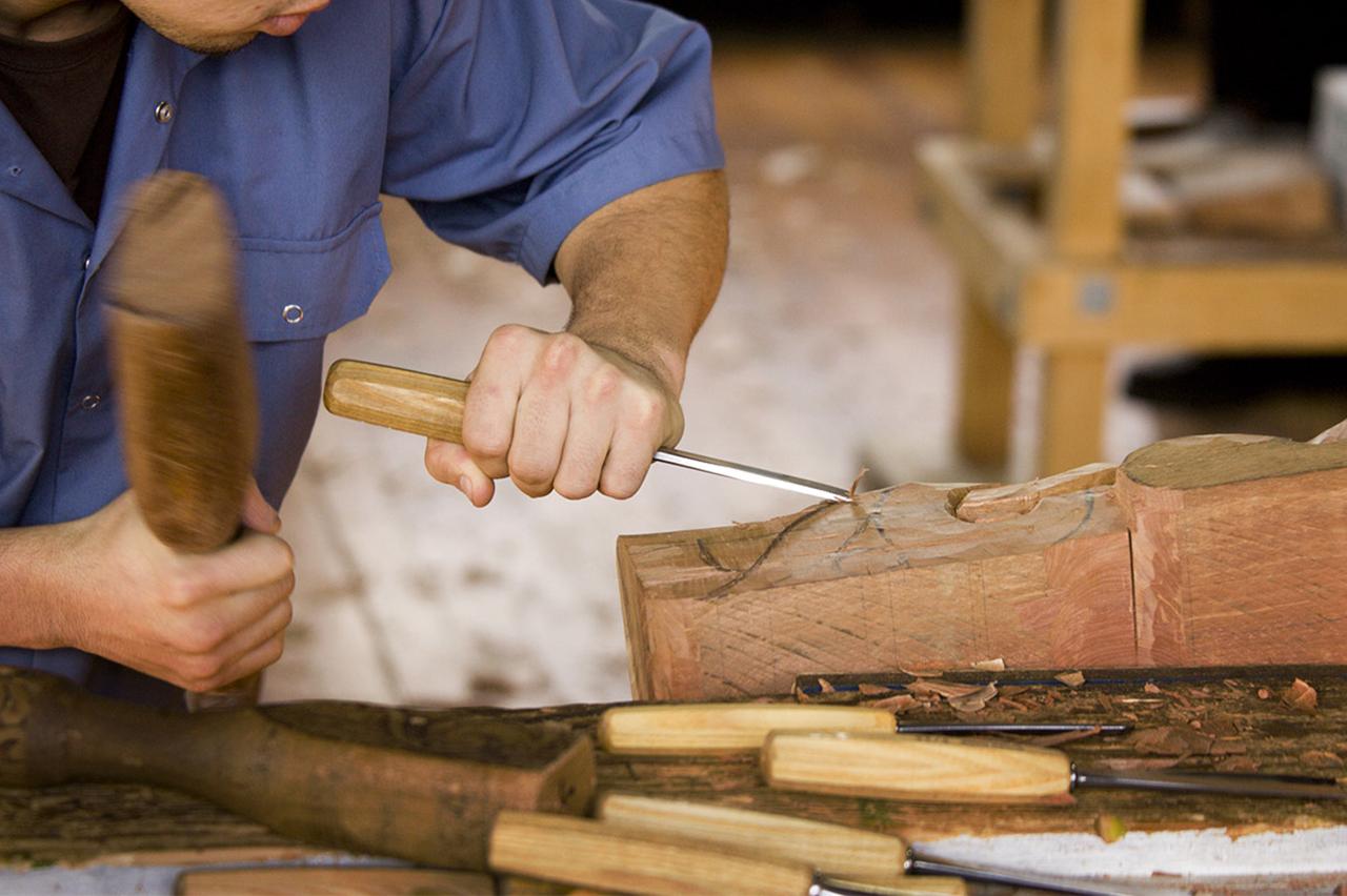 Image montrant Mickaël Buhard en train de travailler un pied de table
